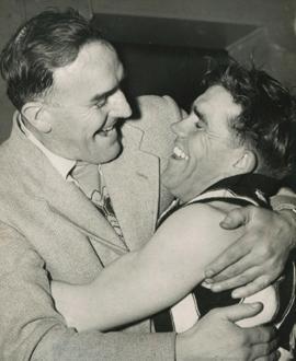 Phonse Kyne embraces Lou Richards after Collingwood secures the 1953 Flag.