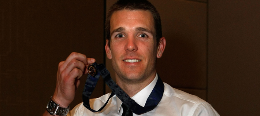 Dane Swan proudly displays his Brownlow Medal, won in 2011.