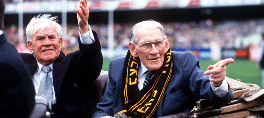 Old enemies become friends: Lou Richards and Jack Dyer enjoy a lap of the MCG in 1999.