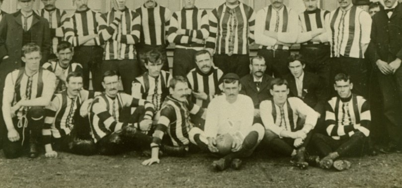 The Magpies of 1899 pose for a pre-game photo ahead of a match against Fitzroy at Victoria Park.