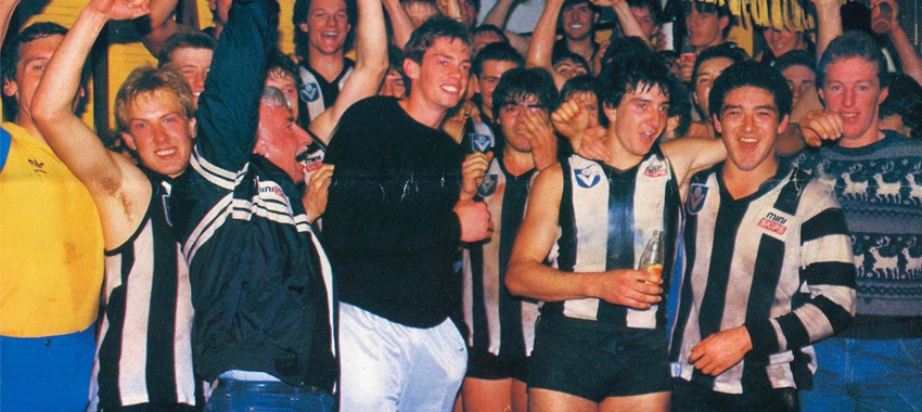 Coach Keith Burns and his players celebrate after Collingwood's Under 19s triumph in 1986. Photo: In Black & White magazine.